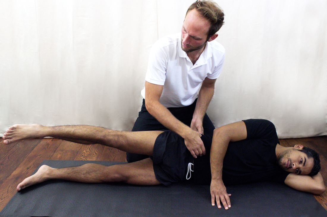 Osteopath Dr Christoph Datler facilitating Pilates matwork exercises for back pain at Blackheath Sports Clinic in London