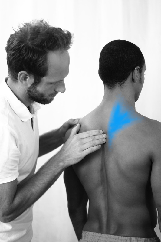 Osteopath Christoph Datler assessing the upper spine of an athlete with upper back pain, neck and shoulder discomfort